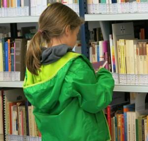 bambina che legge in biblioteca
